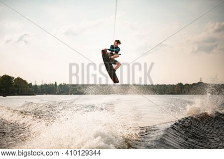 View On Athletic Guy Effectively Jumps On Wakeboard Over The Water