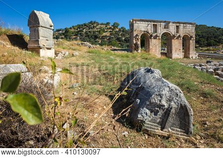 Ruins of rock tombs near city gate of Patara (Arch of Modestus) in ancient Lycia on Mediterranean coast, Turkey