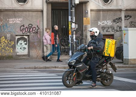 Belgrade, Serbia - February 21, 2021: Glovo Delivery Man Wearing A Face Mask Protective Respirator I