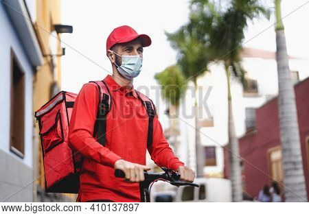 Rider Man Delivering Meal With Electric Scooter In The City While Wearing Face Mask During Corona Vi