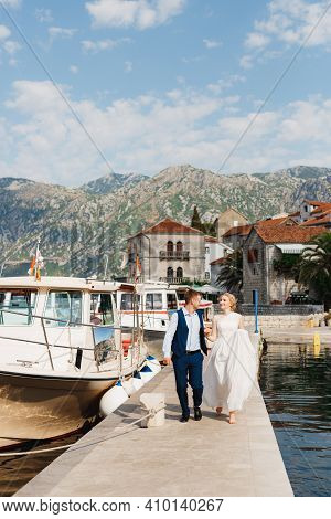 The Bride And Groom Are Walking Along The Pier Holding Hands In The Bay Of Kotor, Tourist Boats Near