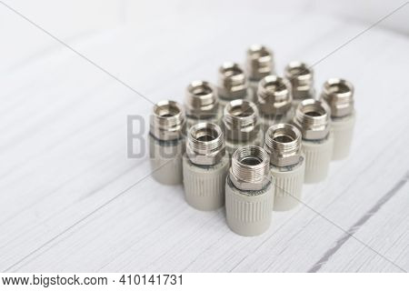 Combined Couplings For Connecting Metal And Polypropylene Water Pipes. Isolated Nuts In Warm Colors