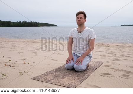 Man Sitting In Yoga Position On Sandy Beach Meditating.
