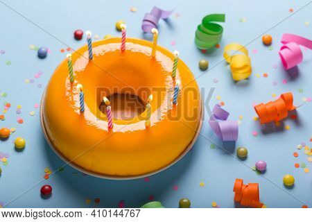Happy Birthday Yellow Cake With Colorful Candles And Decoration On Blue Background. Anniversary And