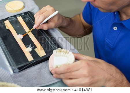 Closeup Of Dental Technician Applying Porcelain