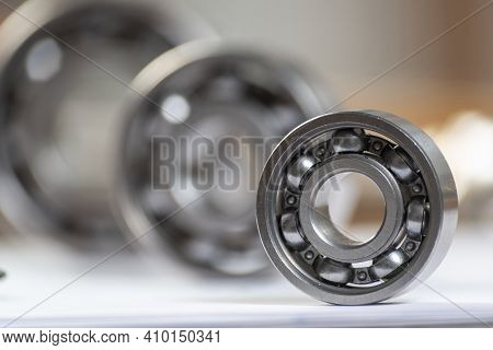 Three Various Ball Bearings Lying On Table. Automotive Spare Part Sale Company. Heavy Industry Engin