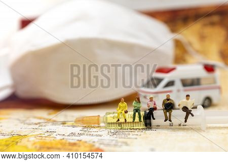 Miniature People Sit Syringe Of Covid-19 Vaccine With Ambulance Car And Medical Mask And  . Vaccine