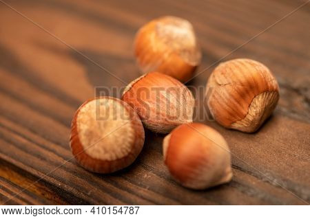 A Few Hazelnuts Scattered On The Wooden Surface. Close-up, Selective Focus