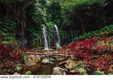 Cascade Waterfall In Tropical Jungle With Red Plans In Bali