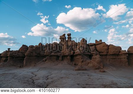 Group Of Reddish Rocks At Goblin Valley State Park, Utah, On A Blue Sky Cloudy Day.