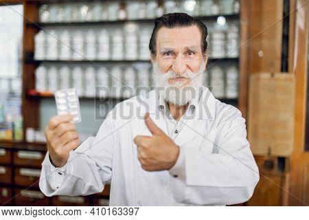 Happy Pharmacist Day. Smiling Joyful Senior Male Pharmacist In White Coat, Standing In Ancient Vinta