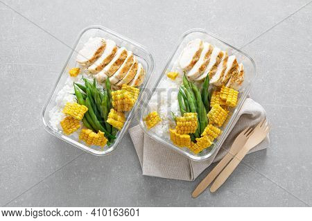 Lunch Box Containers With Grilled Chicken, Rice And Green Beans With Corn