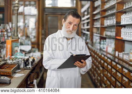 Handsome Eldery Bearded Man Professional Pharmacist, Wearing White Lab Coat, Working In Drugstore As