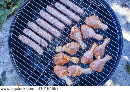Process Cooking Chicken Drumstick And Sausages On Barbecue Grill Outdoors. Picnic, Eating Outdoors.