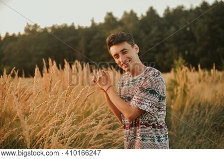 A Gorgeous Photo Of A Man Walking In The Forest Against The Background Of A Wheat Field. A Man On Th