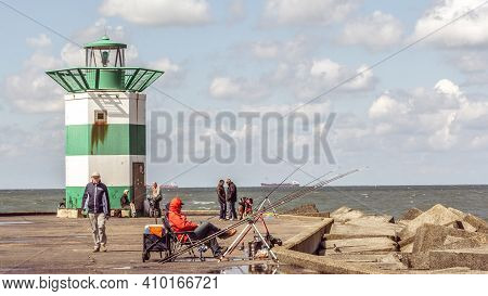 Scheveningen, The Netherlands - May 30, 2015: Fishermen Angling Beside The Lighthouse On The Pier In