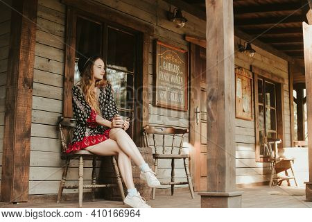 A Woman Is Resting On A Terrace Near A Western House, A Weekend In An Interesting Hotel. Travel Alon