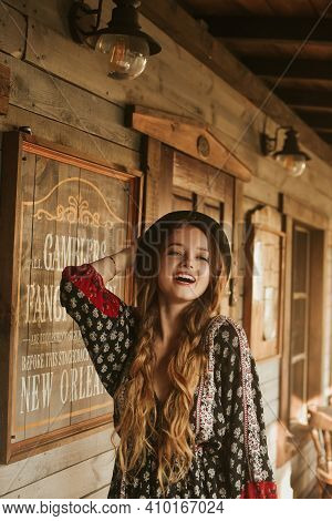 Girl In The Wild West, In Western House. Girl In Hat With Long Cerly Hair Smile. Beautiful Pretty Gi