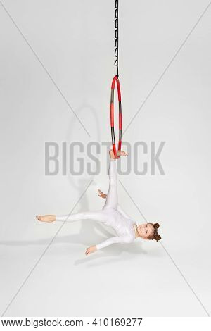 Little Child Girl Gymnast In White Sportwear Shows An Acrobatic Performance On An Aerial Hoop