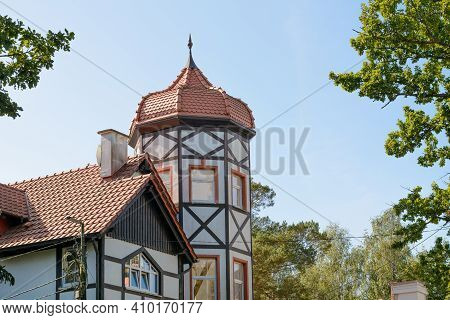 Building Is Tower With Windows And Half-timbered Decoration. Roof Made Of Red Tiles In Form Dome Wit