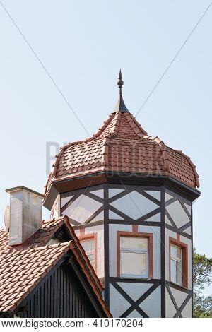 Facade Of House With Tower And Domed Roof Spire At Top. Half-timbered Decoration. German Architectur