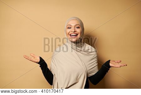Muslim Woman In A Hijab Posing With Her Hands To The Side On Beige Background With Copy Space. Islam
