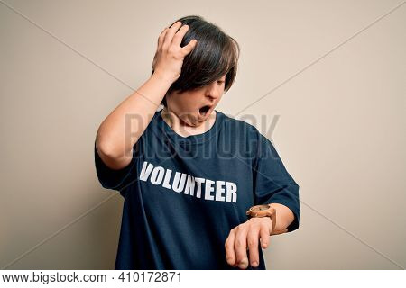 Young down syndrome volunteer woman wearing social care charity t-shirt Looking at the watch time worried, afraid of getting late