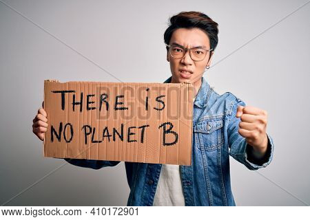 Young handsome chinese activist man protesting asking for care the planet on manifestation annoyed and frustrated shouting with anger, crazy and yelling with raised hand, anger concept