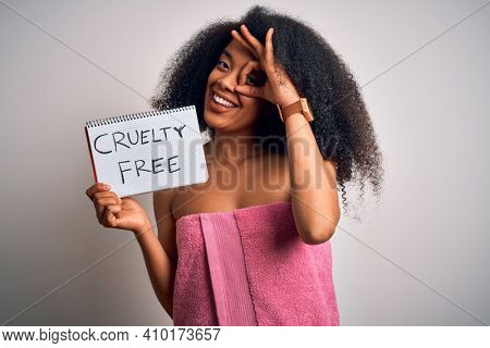Young african american woman with afro hair wearing a towel asking for cruelty free beauty with happy face smiling doing ok sign with hand on eye looking through fingers