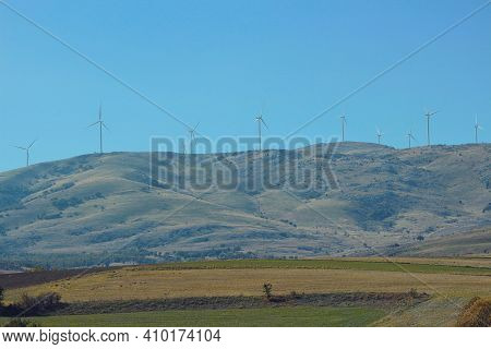 Wind Turbines Located On The Mountain. Wind Turbines Visible On The Road. Wind Turbines On The Mount