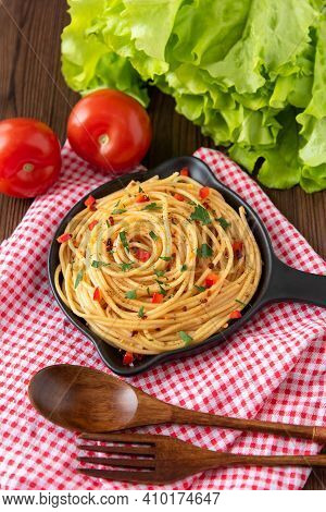 Delicious Hot Pasta With Sauce And Seasonings On A Wooden Background. With A Napkin And Cutlery. Top