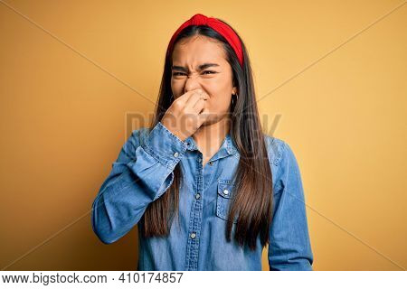 Young beautiful asian woman wearing casual denim shirt and diadem over yellow background smelling something stinky and disgusting, intolerable smell, holding breath with fingers on nose. Bad smell