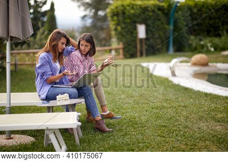 Female friends sitting on a chair and discussing while working on a laptop on a beautiful sunny day in the yard. Friendship, together, outside, yard