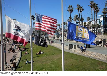 Huntington Beach, California - USA - February 25, 2021: California, American, POW, Huntington Beach Flags fly at Half Mast in Surf City with People enjoying the sunshine in the background. Editorial.