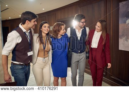 A manager and a team in a hug posing for a photo in a cheerful atmosphere at hotel hallway. Hotel, business, people