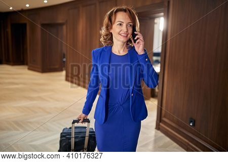 A woman with a suitcase having a business call at hotel hallway. Hotel, business, people