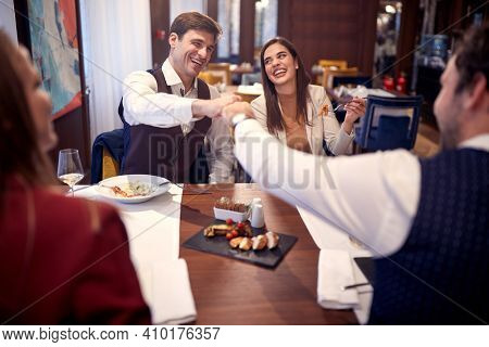 Young business people making a deal in a cheerful atmosphere during a lunch at the restaurant. Business, restaurant, lunch