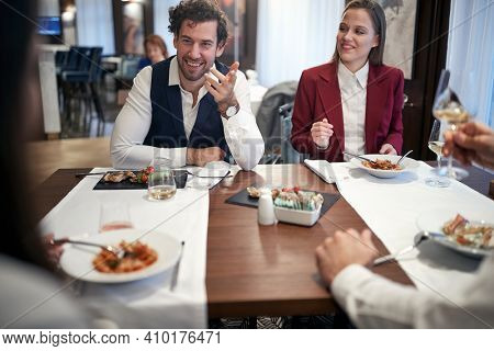 Young business people having pleasant conversation in a cheerful atmosphere during a lunch at the restaurant. Business, restaurant, lunch