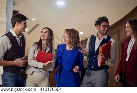 A group of cheerful business people having a friendly talk in a pleasant atmosphere at the hotel hallway. Hotel, business, people