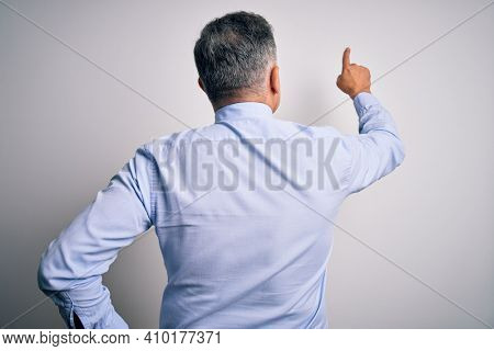 Middle age handsome grey-haired business man wearing elegant shirt and tie Posing backwards pointing ahead with finger hand