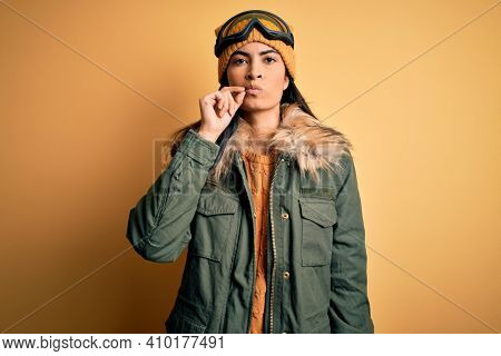 Young beautiful hispanic woman wearing ski glasses and coat for winter weather mouth and lips shut as zip with fingers. Secret and silent, taboo talking