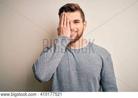 Young handsome blond man with beard and blue eyes wearing casual sweater covering one eye with hand, confident smile on face and surprise emotion.
