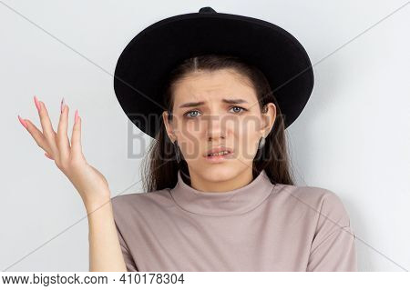 Portrait Of A Confused Frustrated Girl In Sweater Pointing Away And Looking At Camera Isolated Over