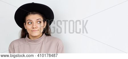 Indoor Shot Of Cute Girl Looking Away, Having Doubtful And Indecisive Face Expression, Pursuing Her