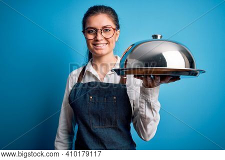 Young beautiful waitress woman with blue eyes holding tray with dome over isolated background with a happy face standing and smiling with a confident smile showing teeth