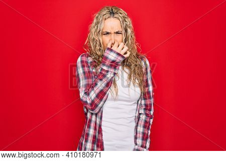 Young beautiful blonde woman wearing casual shirt standing over isolated red background smelling something stinky and disgusting, intolerable smell, holding breath with fingers on nose. Bad smell
