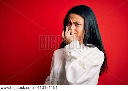 Young beautiful chinese sporty woman wearing sweatshirt over isolated red background smelling something stinky and disgusting, intolerable smell, holding breath with fingers on nose. Bad smell