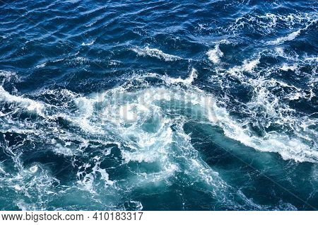 Abstract Background. The Waves Of The Sea Water Meet With Underwater Pointed Rocks, Forming Whirlpoo