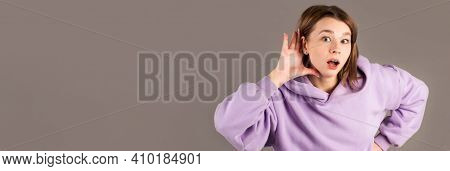 Gossip Woman Hearing With Hand On Ear Isolated On A Gray Background