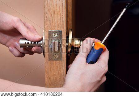 Door Installation, Worker Installs Door Knob, Woodworker Hands Close Up. A Man Spins The Door Handle